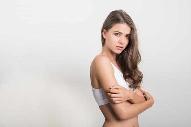 白い背景の上の健康な体を持つ美しい女性