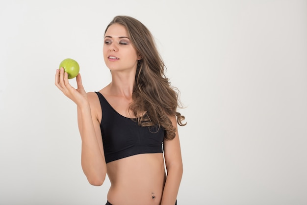 美しさの女性は白で隔離されながら青リンゴを保持