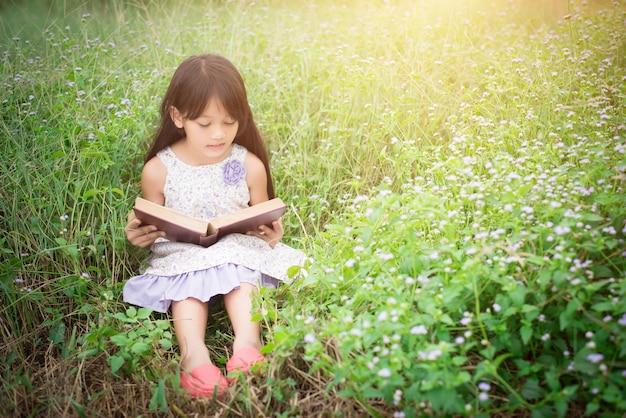 Маленький милый азиатская девушка читает книгу на природе.