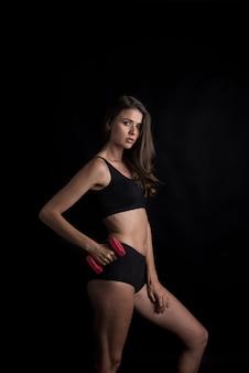 ダンベル運動をする若い美しい女性の肖像画