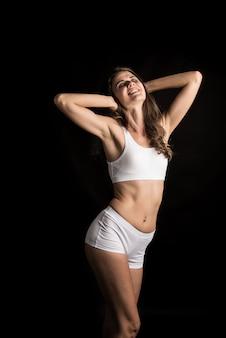 黒の背景に健康な体を持つ美しい女性