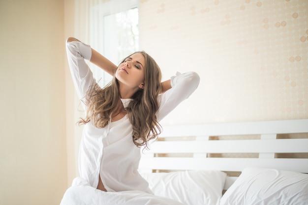 寝室に座っている怠惰な若い女性