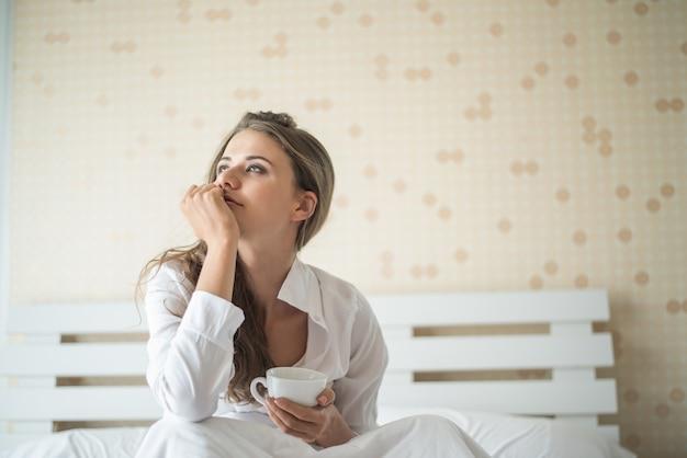 Красивая женщина в своей спальне, пить кофе по утрам