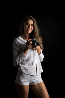 カメラを持つ若い女性写真家のファッションの肖像画