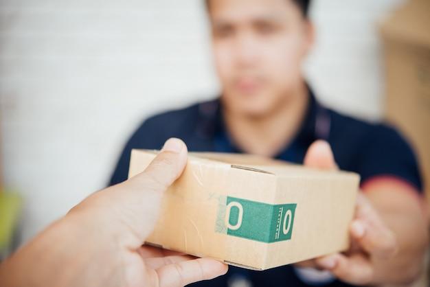 Доставка человек улыбается и держит картонную коробку