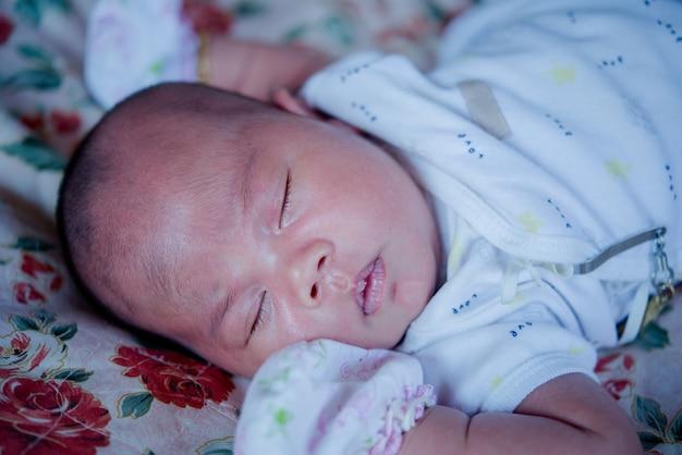 アジアの赤ちゃんがベッドで寝ています。