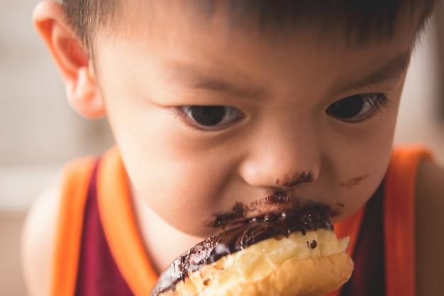 熱いドーナツを食べる空腹の小さな男の子の顔を閉じる