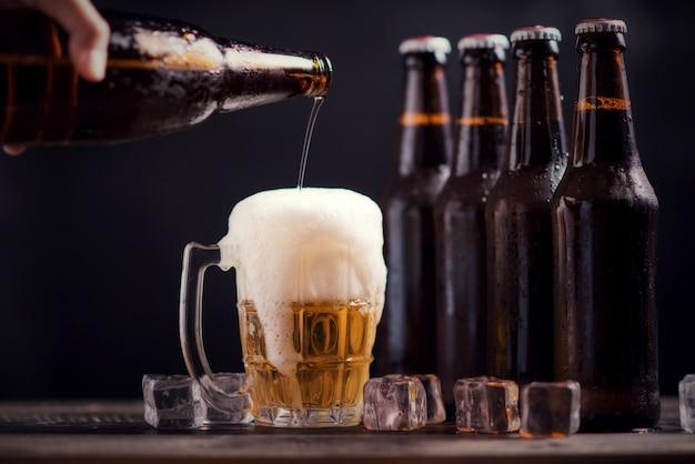 ガラスと氷と暗い背景にビールの入ったガラス瓶