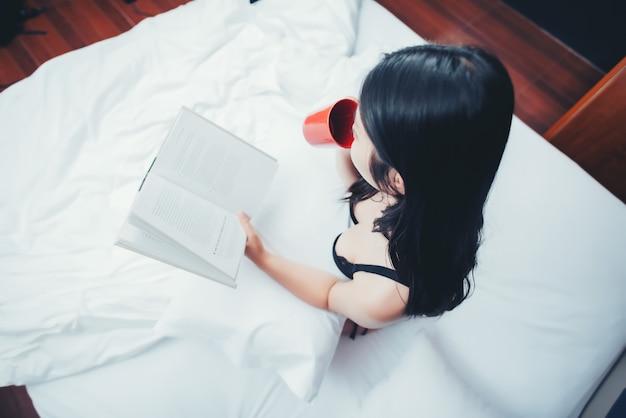 本を読んで、ベッドの中で一杯のコーヒーを保持しているセクシーな女性