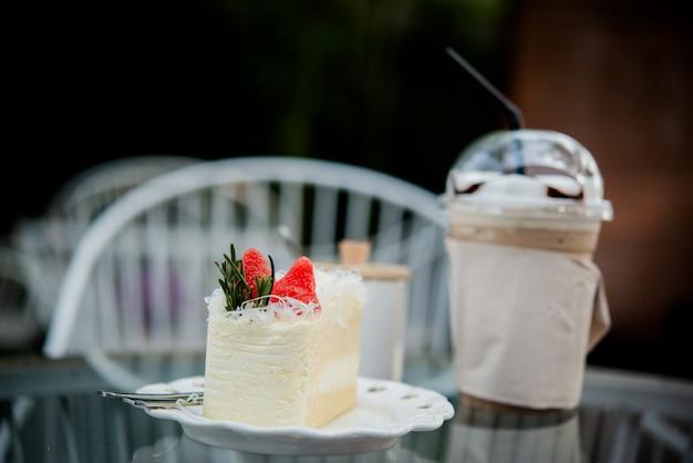 コーヒーショップのテーブルの上のアイスコーヒーとケーキ