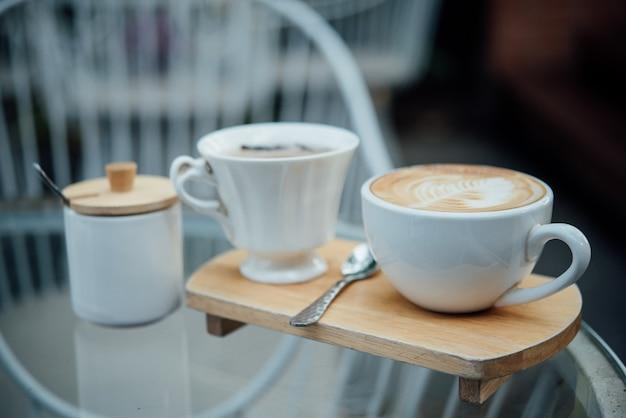 Горячее искусство латте в кофейной чашке на деревянный стол в кафе