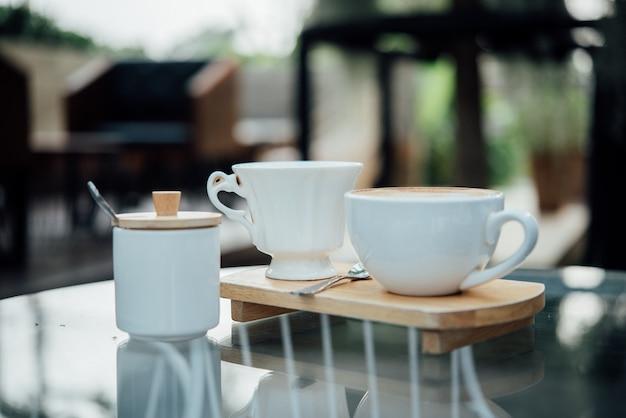 コーヒーショップの木のテーブルにコーヒーカップで熱いラテアート