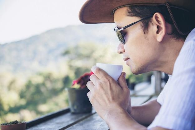 Человек пьет горячий чай с фоном зеленого холма - люди отдыхают в природе концепции