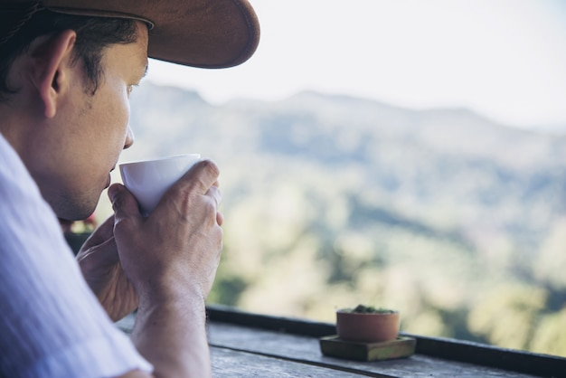 男は緑の丘の背景を持つ熱いお茶を飲む