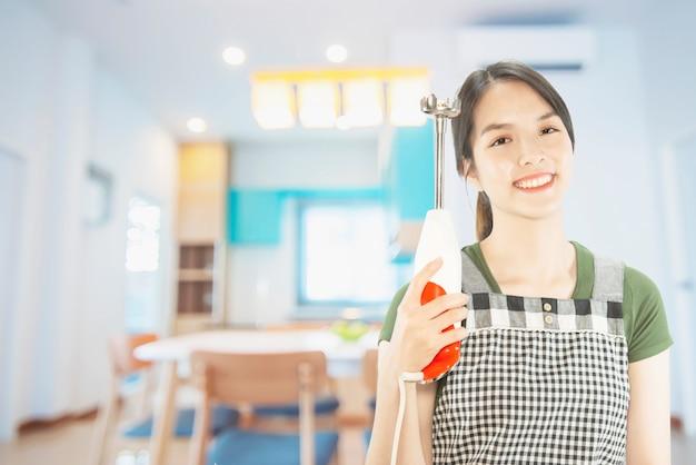 Счастливый леди держит кухню вещи на фоне пространства копирования
