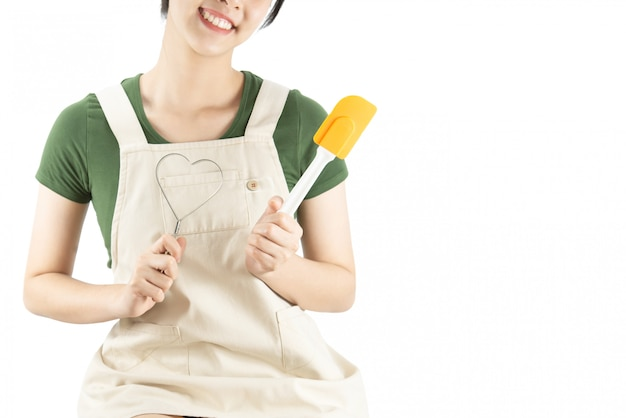 コピースペースの背景の上に台所用品を持って幸せな女