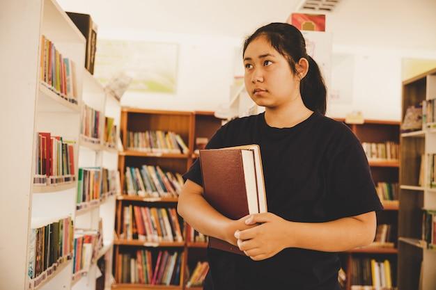 В библиотеке - молодая девушка, ученица с книгами, работает в библиотеке старшей школы.