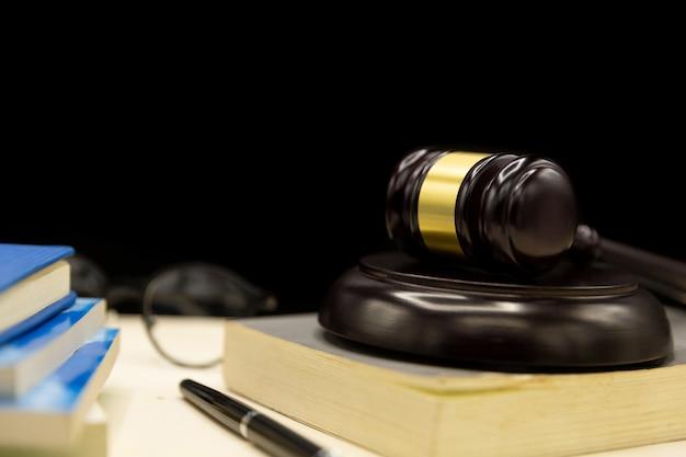 本と木製のテーブル上の裁判官小槌。法と正義の概念の背景。