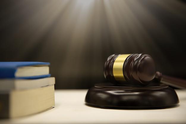 裁判官小槌と木製のテーブルの上の本。法と正義の概念の背景。
