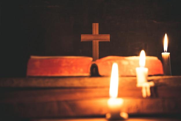 Крест с библией и свечи на старый деревянный стол из дуба. красивый золотой фон.
