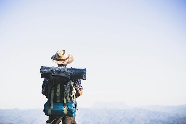 山頂からの観光客。太陽の光。男は太陽の光に対して大きなバックパックを着用します。
