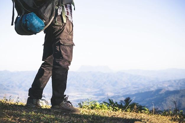 Турист с вершины горы. солнечные лучи. человек носит большой рюкзак против солнечного света