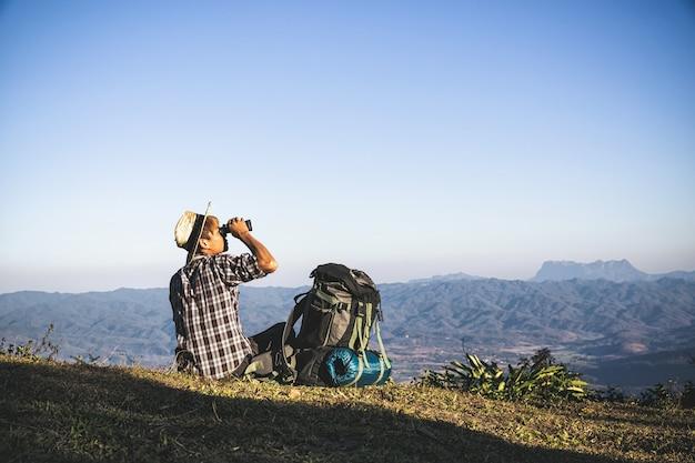 Турист смотрит в бинокль на солнечном облачном небе от вершины горы.