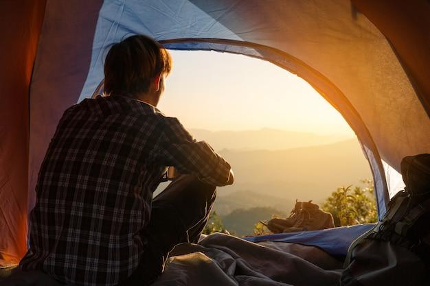 Молодой человек сидит в палатке с чашкой кофе