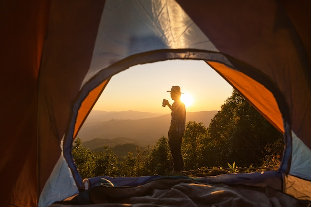 コーヒーカップを持って幸せな男は山の周りのテントの近くに滞在します。
