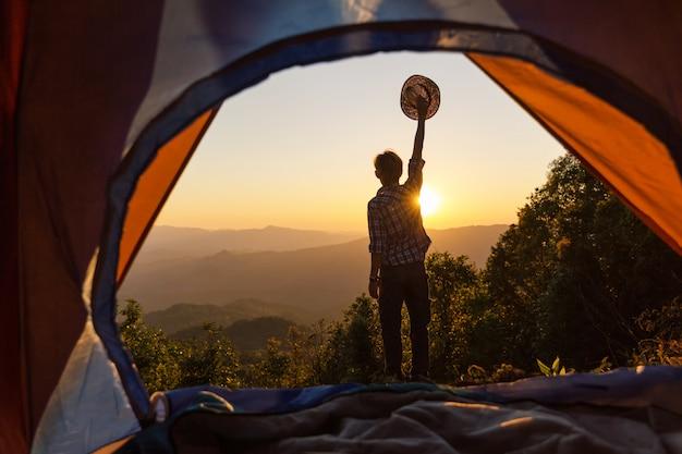 Счастливый человек остаться возле палатки вокруг горы под закат светом неба, наслаждаясь отдыхом и свободой.