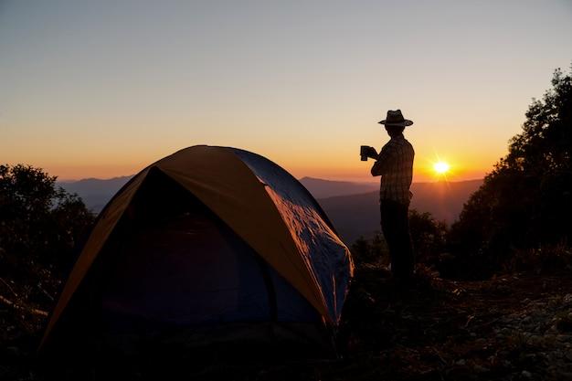 コーヒーカップを持って幸せな男のシルエットは山の周りのテントの近くに滞在します。