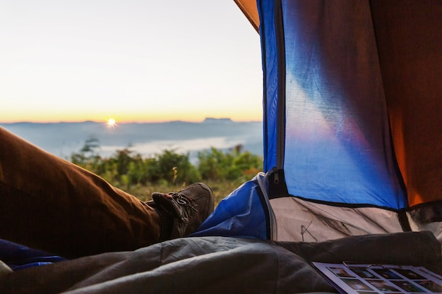 テントの中で足のクローズアップ写真。旅行トレッキング遠征コンセプト