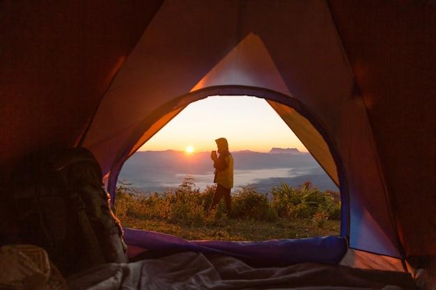 ハイカーは山の中でキャンプの前のオレンジ色のテントとバックパックに