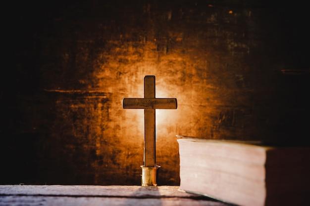 Крест с библией и свечи на старый деревянный стол из дуба.