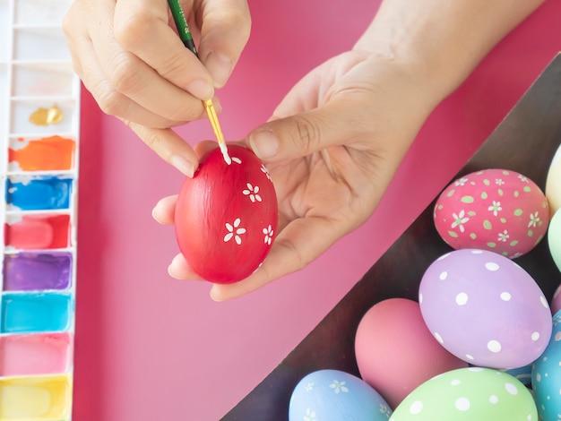 Люди, рисующие красочные пасхальные яйца - концепция праздника пасхи