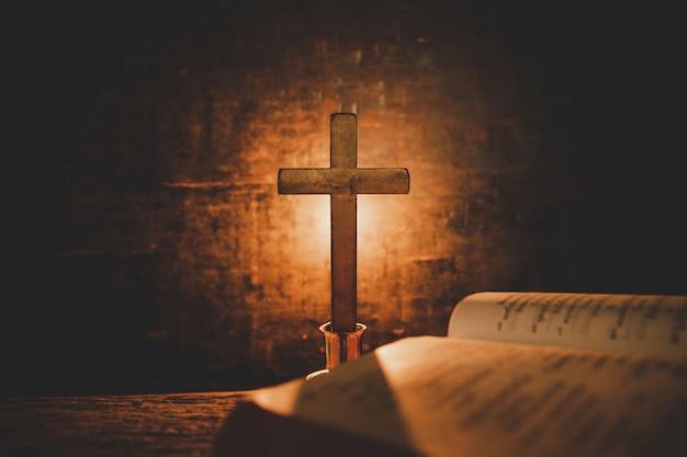 聖書を開き、古いオークの木製のテーブルの上のろうそく。美しい金の背景。宗教の概念