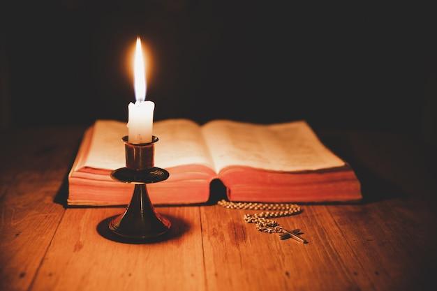 聖書と古いオークの木製のテーブルの上のろうそくを渡ります。美しい金の背景。