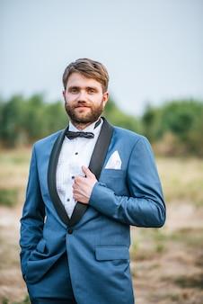 公園で掲示する結婚式のスーツでハンサムな新郎