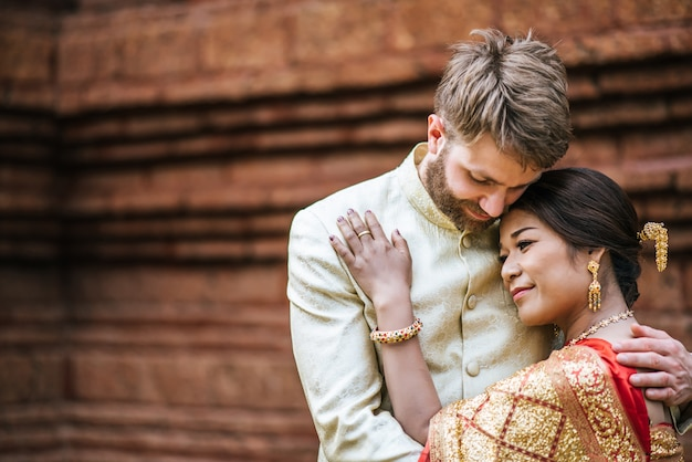 アジアの花嫁と白人の新郎はタイのドレスでロマンチックな時間を過ごす