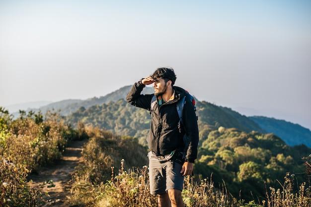 山でのハイキングのバックパックと一緒に旅行する人