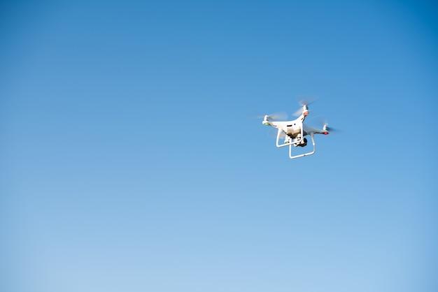 ビデオを録画する白いドローンが空を飛ぶ