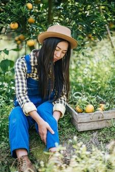 オレンジ色の農園を植える女性