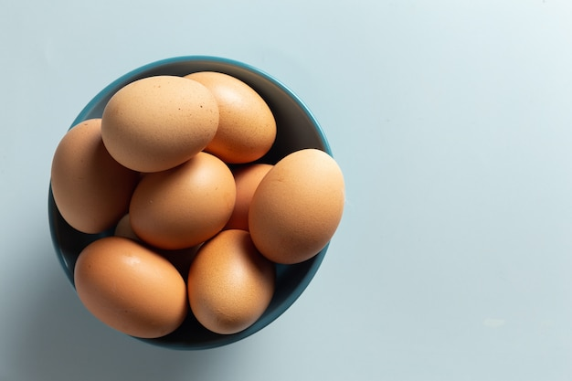 Свежие яйца в миску.