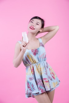 ピンクの背景に製品の瓶を持って美しいアジアの女性。
