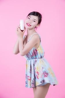Красивая азиатская женщина держа бутылку продукта на розовой предпосылке.