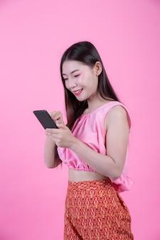 ピンクの背景にスマートフォンを持って美しい女性。