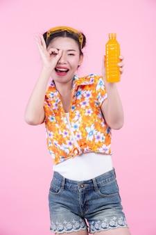 女の子はピンク色の背景にオレンジジュースの瓶を保持しています。
