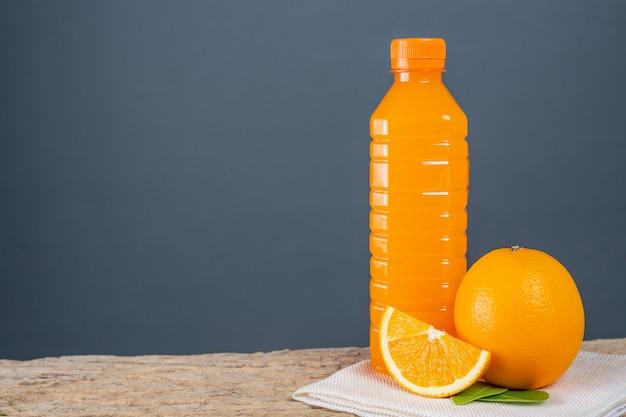 オレンジジュースのグラスを木の上に置きます。