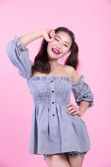 Мода девушка одеваются с жестами на розовом фоне.