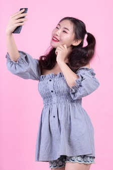 Красивая женщина, держащая смартфон на розовом фоне.